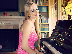 This young blonde cutie has such a beautiful figure, winning smile and sparkling blue eyes that most guys will be a lot more attracted by her femininity than by her musical talent. Thanks God, musical talent doesn't prevent a lass from being also quite naughty.